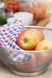 Raw fresh red apple with checkered napkin in sieve Stock Photo