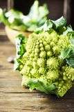 Raw fresh Roman cauliflower on the wooden table. Selective focus Royalty Free Stock Images