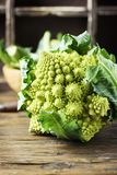 Raw fresh Roman cauliflower on the wooden table. Selective focus Royalty Free Stock Photos