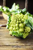 Raw fresh Roman cauliflower on the wooden table. Selective focus Stock Photos