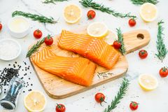 Raw and fresh salmon meat fillet on wooden cutting board. With lemon tomato and other ingredient - Healthy food style Royalty Free Stock Images