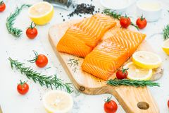 Raw and fresh salmon meat fillet on wooden cutting board. With lemon tomato and other ingredient - Healthy food style Stock Images