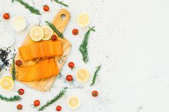Raw and fresh salmon meat fillet on wooden cutting board. With lemon tomato and other ingredient - Healthy food style Stock Photos