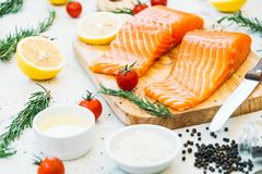 Raw and fresh salmon meat fillet on wooden cutting board. With lemon tomato and other ingredient - Healthy food style Royalty Free Stock Photography