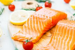 Raw and fresh salmon meat fillet on wooden cutting board. With lemon tomato and other ingredient - Healthy food style Stock Image