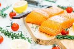 Raw and fresh salmon meat fillet on wooden cutting board. With lemon tomato and other ingredient - Healthy food style Royalty Free Stock Image