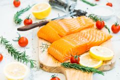 Raw and fresh salmon meat fillet on wooden cutting board. With lemon tomato and other ingredient - Healthy food style Stock Photo