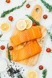 Raw and fresh salmon meat fillet on wooden cutting board. With lemon tomato and other ingredient - Healthy food style Royalty Free Stock Photo