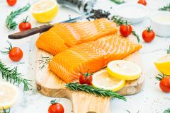Raw and fresh salmon meat fillet on wooden cutting board. With lemon tomato and other ingredient - Healthy food style Royalty Free Stock Photos