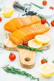 Raw and fresh salmon meat fillet on wooden cutting board. With lemon tomato and other ingredient - Healthy food style Stock Photography