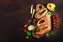 Raw fresh salmon steak with vegetables. Ingredients for cooking on brown background. Space for text. Diet and healthy. Food concept. Banner Stock Photos