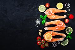 Raw fresh salmon steak with vegetables. Ingredients for cooking on brown background. Space for text. Diet and healthy. Food concept. Banner Royalty Free Stock Images