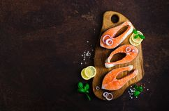 Raw fresh salmon steak with vegetables. Ingredients for cooking on brown background. Space for text. Diet and healthy. Food concept. Banner Stock Image