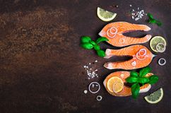 Raw fresh salmon steak with vegetables. Ingredients for cooking on brown background. Space for text. Diet and healthy. Food concept. Banner Stock Photography