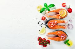 Raw fresh salmon steak with vegetables. Ingredients for cooking on white background. Space for text. Diet and healthy. Food concept. Banner Royalty Free Stock Photo