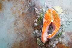 Raw fresh salmon or trout steak on ice, rich in omega-3 oil, with lime, thyme and olive oil on a blue rusty background. Healthy. And diet food. Top view with stock photos