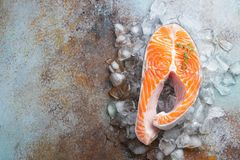 Raw fresh salmon or trout steak on ice, rich in omega-3 oil, with lime, thyme and olive oil on a blue rusty background. Healthy. And dietary food. Top view with royalty free stock image