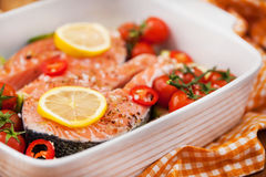 Raw fresh salmon and vegetables before cooking. Raw fresh delicious salmon, cherry tomatoes, chili, zucchini and lemon in pan, ready to cook Royalty Free Stock Photos