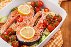 Raw fresh salmon and vegetables before cooking. Raw fresh delicious salmon, cherry tomatoes, chili, zucchini and lemon in pan, ready to cook Royalty Free Stock Image