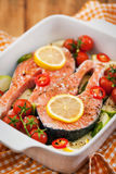 Raw fresh salmon and vegetables before cooking. Raw fresh delicious salmon, cherry tomatoes, chili, zucchini and lemon in pan, ready to cook Royalty Free Stock Photo