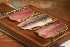 Raw Fresh Sardine Fillet. Over a wooden board Stock Photo