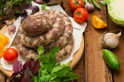 Raw fresh sausages in a white plate on a wooden background. Top view. Close-up. Raw fresh sausages in a white plate on a wooden background. Close-up. Top view Stock Image