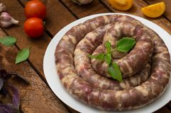 Raw fresh sausages in a white plate on a wooden background. Top view. Close-up. Raw fresh sausages in a white plate on a wooden background. Close-up. Top view Stock Photography