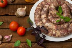 Raw fresh sausages in a white plate on a wooden background. Top view. Close-up. Raw fresh sausages in a white plate on a wooden background. Close-up. Top view Stock Photo