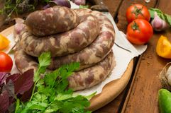 Raw fresh sausages in a white plate on a wooden background. Top view. Close-up. Raw fresh sausages in a white plate on a wooden background. Close-up. Top view Royalty Free Stock Images