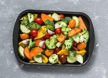 Raw fresh seasonal vegetables on a baking sheet. Sweet potato, zucchini, sweet pepper, cherry tomatoes, garlic, broccoli cabbage,. Olive oil, rose salt Stock Images