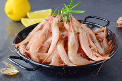 Raw fresh shrimps in a black metal bowl with rosemary on a grey background. Mediterannean lifestyle. Healthy food. Stock Photo