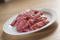 Raw fresh sliced beef for beefsteaks in plate on kitchen table Royalty Free Stock Photography