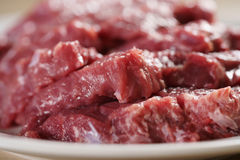 Raw fresh sliced beef for beefsteaks in plate on kitchen table Stock Image