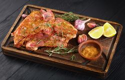 Raw fresh spare lamb ribs on board. Raw fresh spare lamb ribs marinated to be cooked with rosemary, thyme, mix of spices, garlic and lemon slices on wooden Royalty Free Stock Photo