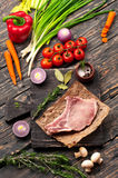 Raw fresh steak on the bone with vegetables. On a dark wooden rustic background. Top view with copy space Stock Images