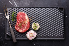 Raw fresh Steak Ribeye on cast iron grill surface Royalty Free Stock Photo