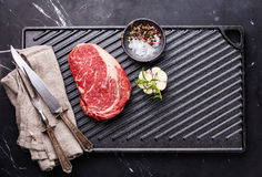 Raw fresh Steak Ribeye on cast iron grill surface Stock Photography