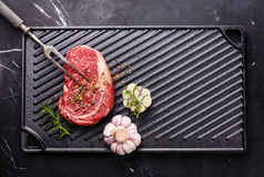 Raw fresh Steak Ribeye on cast iron grill surface Royalty Free Stock Photography