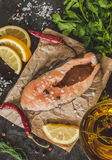Raw fresh steak trout fish on paper, around greens, leaves, lett Stock Photo