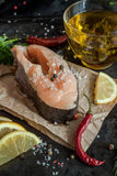 Raw fresh steak trout fish on paper, around greens, leaves, lett Stock Photography