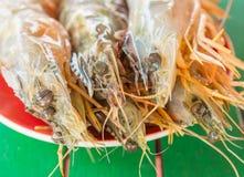 Raw fresh tiger prawn on red dish. Close up Stock Image