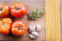 Raw fresh tomatoes with spaghetti, garlic and herbs stock images