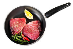 Raw fresh tuna fillet with herbs, salt and lemon  in a frying pa. N, isolated on white background. Tuna steak Stock Images