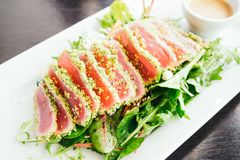 Tuna salad. Raw and fresh tuna meat with vegetable salad in white plate - Healthy food style Stock Photo