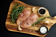 Raw fresh uncooked chicken breast meat fillet dish with rosemary, pepper, salt and garlic on wooden board and black background. stock images