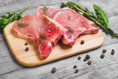 Raw fresh uncooked Pork Meat steak. On bone, cutting chopping board for cutting raw steaks of pork lettuce and pepper on light white background wooden Stock Photo