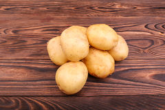 Raw, fresh and uncooked potatoes on a dark brown wooden background. Fresh vegetables. Natural agriculture food. New potatoes. Royalty Free Stock Photography