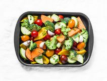 Raw fresh vegetables on a baking sheet. Sweet potato, zucchini, sweet pepper, cherry tomatoes, garlic, broccoli cabbage-ingredient. S for healthy vegetarian Royalty Free Stock Photos