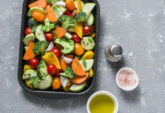 Raw fresh vegetables on a baking sheet. Sweet potato, zucchini, sweet pepper, cherry tomatoes, garlic, broccoli cabbage, olive oil. Rose salt - ingredients for Stock Photos