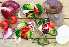 Raw fresh vegetables - broccoli, eggplant, peppers, tomatoes, onions, garlic in portion pots. Preparation of the garnish Stock Photo